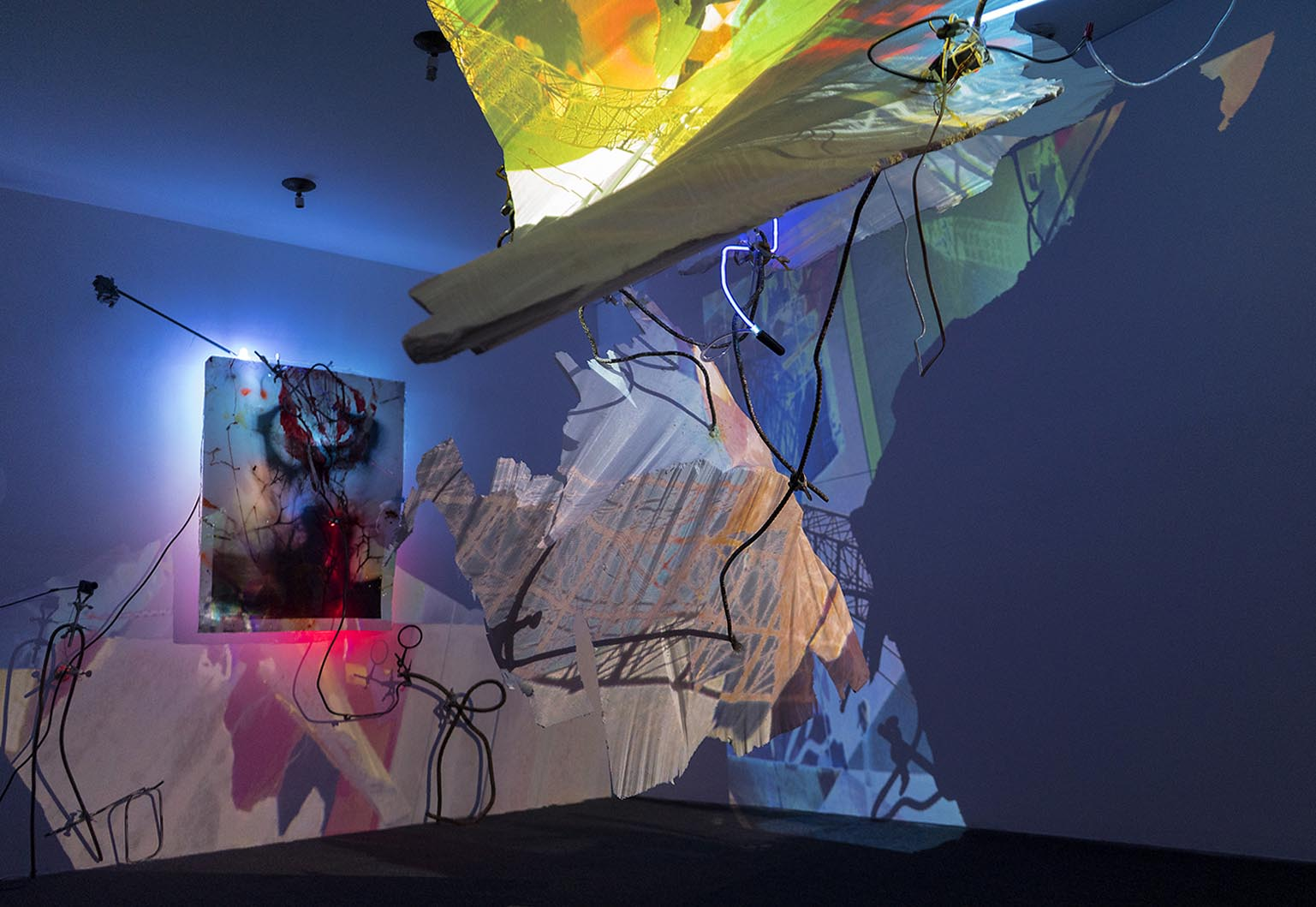 """""""Dear Volunteers"""", collaborative installation with John Schlesinger, AC Institute, NY, 1,300 SF, 2016. Materials: neon, rebar, styrofoam, painted photos cast in epoxy, lab clamps, security cameras, projectors, computer, algorithmically generated interactive projection-mapped video."""